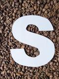bokstav S i vit och bakgrund med grillade kaffebönor, bakgrund och textur royaltyfria foton