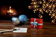 Bokstav till Santa Claus nära gåvan och stearinljusen Royaltyfri Fotografi