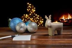 Bokstav till Santa Claus nära leksakerna och stearinljusen Arkivfoton