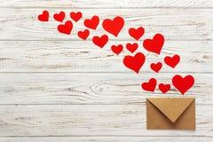 Bokstav till Valentine Day Kuvert för förälskelsebokstav med röda hjärtor på träbakgrund Arkivfoton