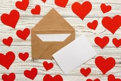 Bokstav till Valentine Day Kuvert för förälskelsebokstav med röda hjärtor på träbakgrund arkivbilder