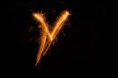 Bokstav V som göras av tomtebloss på svart Arkivfoton