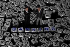Bokstaven blockerar stavningsbankrörelsen med modellaffärsmän Royaltyfria Foton