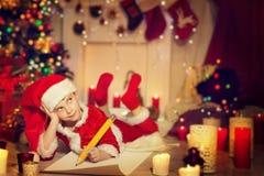 Bokstaven för barnhandstiljul, den lyckliga ungen skriver Santa Wish List royaltyfria bilder