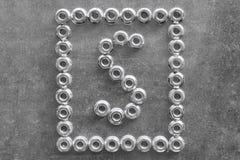 Bokstaven s av det engelska eller latinska alfabetet fodrade med metallmuttrar Royaltyfri Fotografi