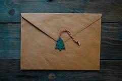 bokstaven till Santa Claus, kuvert med träjuldekoren i form av vaxskyddsremsan, lägenhet lägger på mörk träbakgrund royaltyfri bild