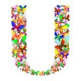 Bokstaven U utgjorde av massor av fjärilar av olika färger Arkivbild