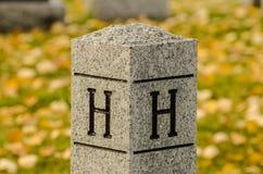 BokstavsH som snidas på en stenstolpe Arkivfoton