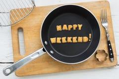 Bokstavskex uttrycker LYCKLIGA HELG- och matlagningutrustningar Royaltyfria Bilder
