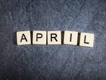Bokstavstegelplattor på svart kritiserar bakgrund som stavar April arkivfoto