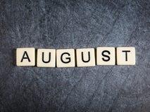 Bokstavstegelplattor på svart kritiserar bakgrund som stavar Augusti fotografering för bildbyråer