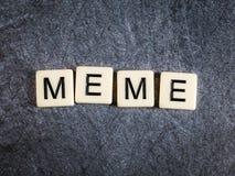 Bokstavstegelplattor på svart kritiserar bakgrund som stavar Meme fotografering för bildbyråer