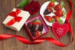 Boksuje z smakowita czekolada zamaczającym bukietem kwiaty na stole i truskawkami fotografia royalty free