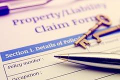Bolígrafo azul, dos llaves de cobre amarillo antiguas y una propiedad/una forma de demanda de responsabilidad en un tablero imagen de archivo