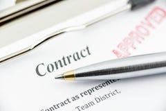 Bolígrafo azul en un contrato aprobado imagenes de archivo