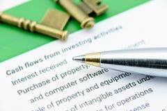 Bolígrafo azul en una declaración de los flujos de liquidez en la parte de flujos de liquidez de invertir actividades foto de archivo libre de regalías