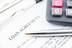 Bolígrafo azul y una calculadora en un acuerdo de préstamo fotos de archivo