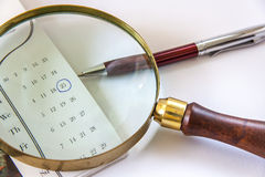 Bolígrafo de la lupa y en calendario Foto de archivo