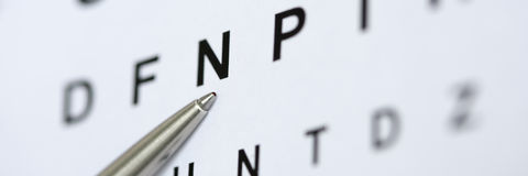 Bolígrafo de plata que señala a la letra en tabla del control de la vista Imagenes de archivo