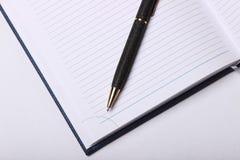 Bolígrafo negro que miente en un cuaderno Imagen de archivo
