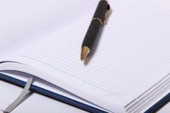 Bolígrafo negro que miente en un cuaderno Foto de archivo