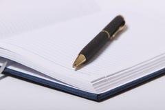 Bolígrafo negro que miente en un cuaderno Imágenes de archivo libres de regalías