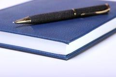 Bolígrafo negro que miente en un cuaderno Imagen de archivo libre de regalías