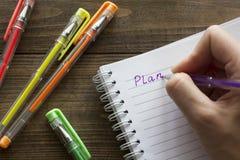 Bolígrafos, cuaderno y mano multicolores Imagen de archivo