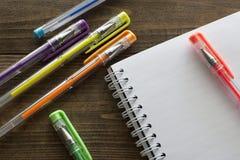 Bolígrafos y cuaderno multicolores Imagen de archivo