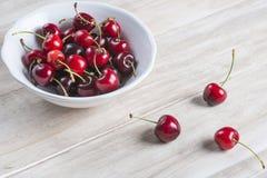 Bol blanc de cerises sur la table Photo libre de droits