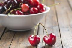 Bol blanc de cerises sur la table Photo stock