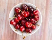 Bol blanc de cerises sur le bois Photographie stock libre de droits