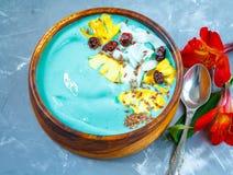 Bol bleu de smoothie de spirulina avec l'ananas et la noix de coco Images stock