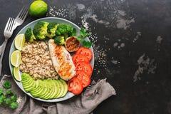 Bol de Bouddha de quinoa, de poulet grillé, d'avocat, de brocoli, de chaux et de tomate sur le fond en pierre foncé Salade saine  photographie stock