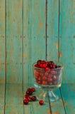 Bol de canneberges sur un fond en bois de turquoise Image stock