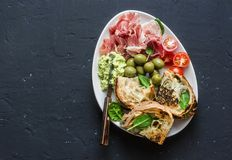 Bol de casse-croûte - le prosciutto, olives, tomates-cerises, immersion d'avocat, a grillé des sandwichs à épinards de mozzarella Photos stock