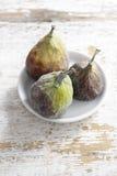 Bol de figues sur une table en bois blanche Photographie stock libre de droits