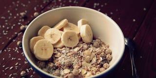Bol de granola avec la banane, les raisins secs et le plan rapproché nuts Image libre de droits