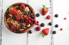 Bol de granola faite maison avec du yaourt et les baies fraîches sur en bois images stock