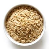 Bol de riz brun à grain long sur le blanc images libres de droits