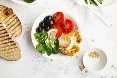 Bol de riz brun de haloumi de fromage avec des tomates, des olives, le citron et des pignons Vue supérieure Photographie stock libre de droits