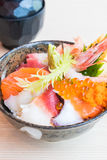 Bol de riz japonais avec des fruits de mer de sashimi sur le dessus Images stock