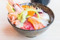 Bol de riz japonais avec des fruits de mer de sashimi sur le dessus Image stock