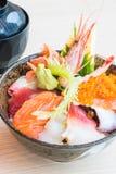Bol de riz japonais avec des fruits de mer de sashimi sur le dessus Photo stock