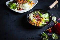 Bol de salade végétale sur le fond noir image stock