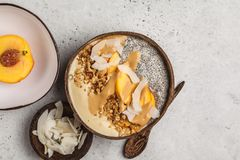 Bol de Smoothie avec le pudding, la pêche, la noix de coco et la granola de chia dans a images libres de droits