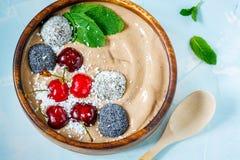 Bol de smoothie de chocolat avec la cerise, la menthe et les boules d'énergie Photos libres de droits