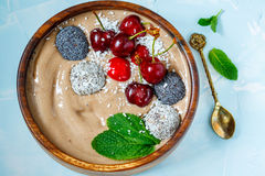 Bol de smoothie de chocolat avec la cerise, la menthe et les boules d'énergie Photographie stock libre de droits