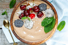 Bol de smoothie de chocolat avec la cerise, la menthe et les boules d'énergie Images libres de droits