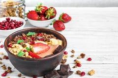 Bol de smoothie de protéine de banane de chocolat avec des graines de granola, de fraise et de grenade sur la table en bois blanc photo libre de droits